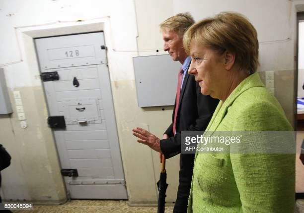 German Chancellor Angela Merkel is accompanied by German historian and director of the BerlinHohenschönhausen Memorial Hubertus Knabe as she visits...