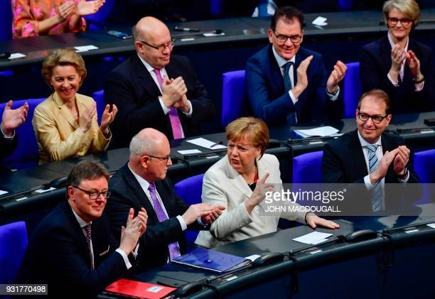 German Chancellor Angela Merkel is applauded by parliamentary group leader of the conservative CDU faction Volker Kauder the parliamentary group...