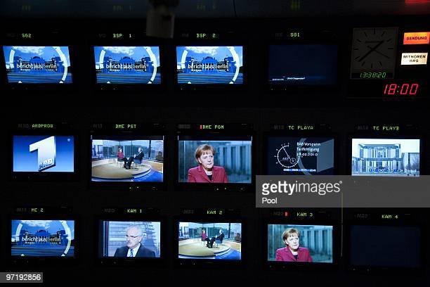 German Chancellor Angela Merkel is dispalyed on different TV screens at public German television channel ARD during an interview broadcasting...