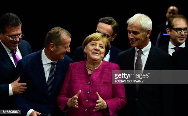 TOPSHOT German Chancellor Angela Merkel is flanked by Volkswagen chairman Matthias Mueller and Volkswagen board member Herbert Diess as she visits...