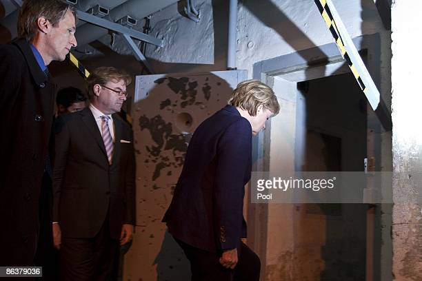 German Chancellor Angela Merkel is followed by current prison memorial director Hubertus Knabe and State Secretary Andre Schmitz while touring the...
