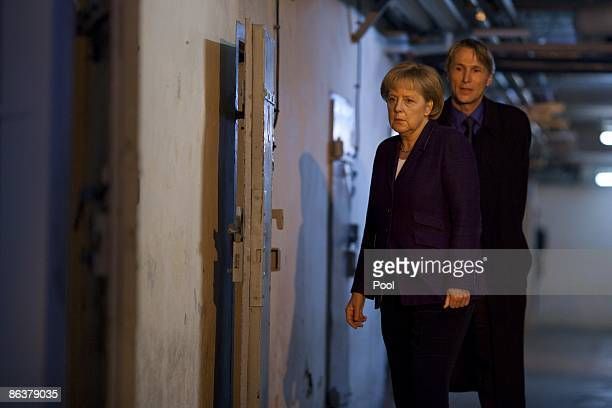 German Chancellor Angela Merkel is followed by current prison memorial director Hubertus Knabe while touring the former prison of the East German...