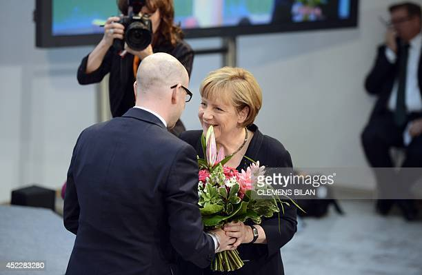 German Chancellor Angela Merkel is given a bouquet of flowers by her Christian Democratic Union party's secretary general Peter Tauber during a...