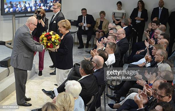 German Chancellor Angela Merkel is given a bouquet of flowers by Chief of Staff Peter Altmaier during a festive event to celebrate Merkel's 60th...