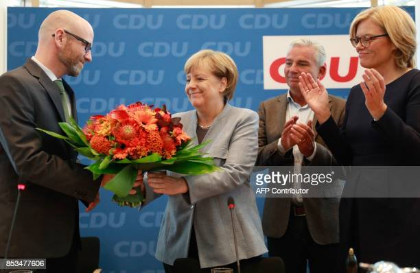 German Chancellor Angela Merkel is given a bouquet of flowers by the secretary general of her conservative Christian Democratic Union party Peter...