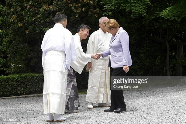 German Chancellor Angela Merkel is greet by Shinto priests as he visit the IseJingu Shrine on May 26 2016 in Ise Japan In the twoday summit the G7...