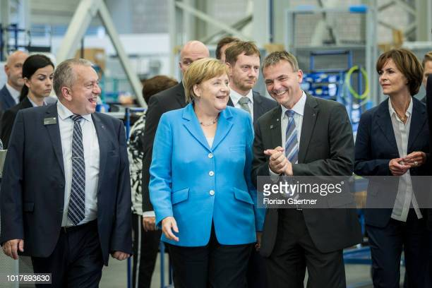 German Chancellor Angela Merkel is pictured with Harry Thonig managing director of TRUMPF and Roger Kluth managing director of TRUMPF during their...