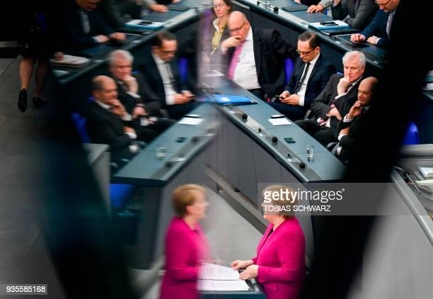 TOPSHOT German Chancellor Angela Merkel is reflected as German Finance Minister and ViceChancellor Olaf Scholz Interior Minister Horst Seehofer...
