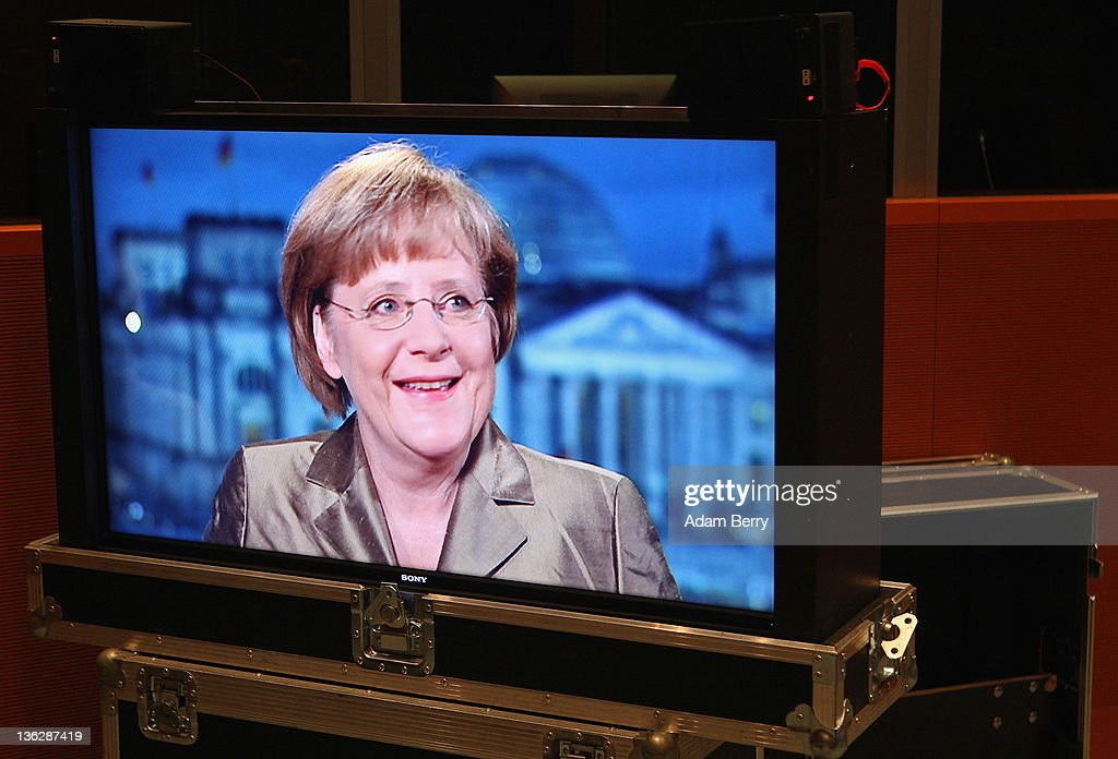 German Chancellor Angela Merkel is seen on a television monitor during a screen test prior to delivering her New Year's television address to the nation at the federal chancellery (Bundeskanzleramt) on December 30, 2011 in Berlin, Germany.