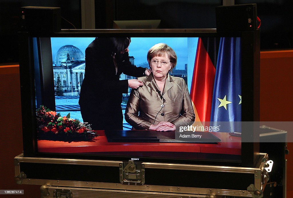 German Chancellor Angela Merkel is seen on a television monitor being prepared for her New Year's television address to the nation during a screen test at the federal chancellery (Bundeskanzleramt) on December 30, 2011 in Berlin, Germany.
