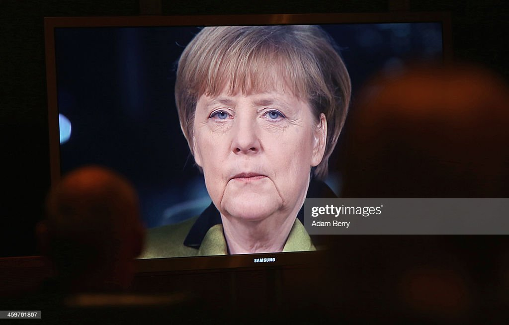 German Chancellor Angela Merkel is seen speaking on a video monitor as she gives her New Year's television address to the nation at the federal chancellery (Bundeskanzleramt) on December 30, 2013 in Berlin, Germany.
