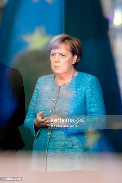 """German Chancellor Angela Merkel is seen through a window as she waits before welcoming Ethiopian Prime Minister on the sidelines of the """"Compact with..."""