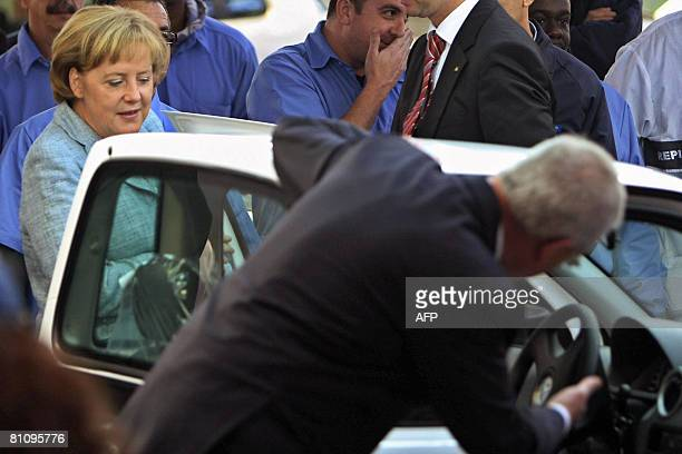 German Chancellor Angela Merkel is shown a car by Volkswagen' s CEO Martin Winterkorn during her visit to the VW plant on May 15 in Sao Bernardo do...