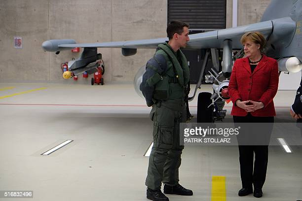 German Chancellor Angela Merkel is shown a Eurofighter jet at the German Air Force airbase Noervenich near Cologne on March 21 2016 / AFP / PATRIK...