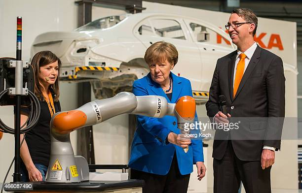German Chancellor Angela Merkel is testing a robotic arm standing next to a worker and KUKA CEO Till Reuter while visiting the KUKA industrial...