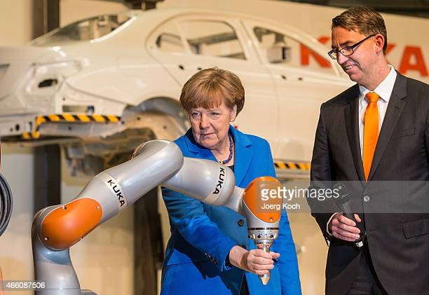 German Chancellor Angela Merkel is testing a robotic arm standing next to KUKA CEO Till Reuter while visiting the KUKA industrial robotics factory on...