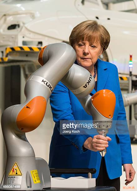 German Chancellor Angela Merkel is testing a robotic arm while visiting the KUKA industrial robotics factory on March 13 2015 in Augsburg Germany...