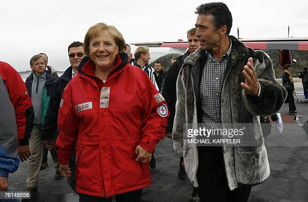 German Chancellor Angela Merkel is welcomed by Denmark's Prime Minister Anders Fogh Rasmussen at the airport of Kangerlussuaq Greenland 16 August...