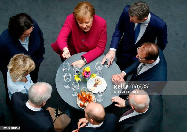 German Chancellor Angela Merkel jokes with CSU leader and designated German Interior Minister Horst Seehofer as German Finance Minister and...