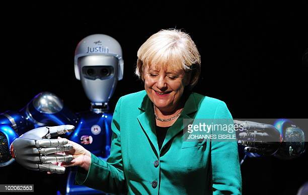 German Chancellor Angela Merkel jokes with 'SpaceJustin' a humanoid space robot at the International Aerospace Exhibition on June 8 2010 at the...