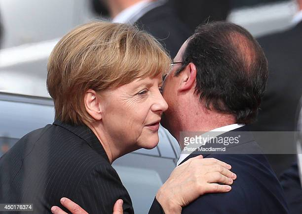 German Chancellor Angela Merkel kisses French President Francois Hollande after the International Ceremony at Sword Beach to commemorate the 70th...