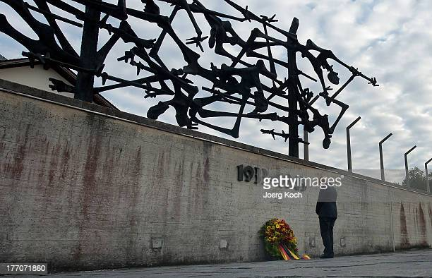 German Chancellor Angela Merkel lays a wreath while visiting the Dachau concentration camp memorial on August 20 2013 in Dachau Germany Merkel's...