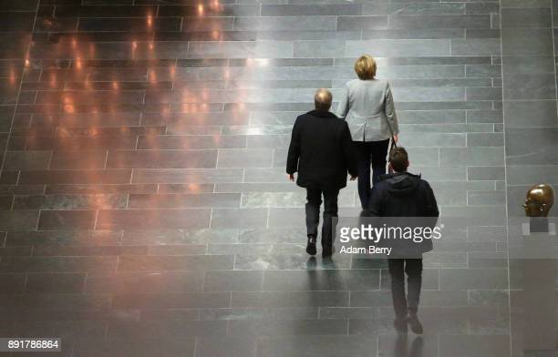 German Chancellor Angela Merkel leaves a meeting in the Bundestag with leaders of the SPD CSU and her own party on December 13 2017 in Berlin Germany...