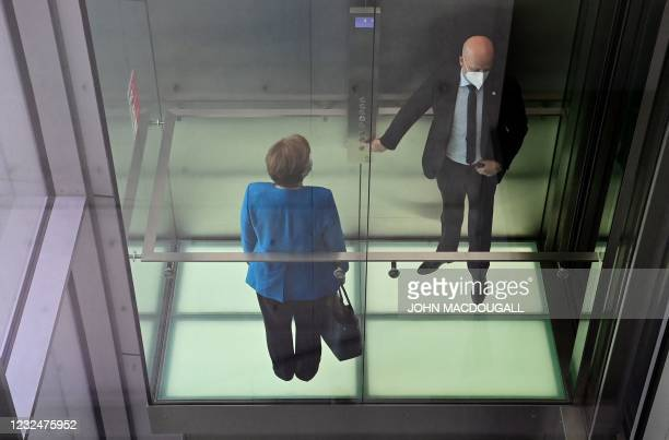 German Chancellor Angela Merkel leaves the meeting room with a security guard by elevator after testifying in front of a parliamentary inquiry...