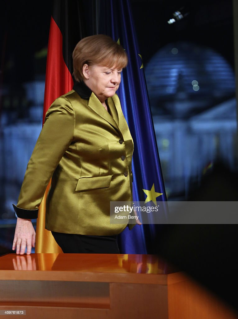 German Chancellor Angela Merkel leaves the room after giving her New Year's television address to the nation at the federal chancellery (Bundeskanzleramt) on December 30, 2013 in Berlin, Germany. Merkel spoke of the challenges and priorities set for the German government for 2014.