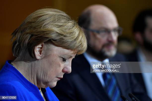 German Chancellor Angela Merkel listens during a joint press conference with the leader of the Social Democratic Party Martin Schulz and the leader...