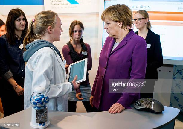 German Chancellor Angela Merkel listens to a girls as she visits a stand of a Telemedicine company as part of the Girls' Day at the Chancellery in...