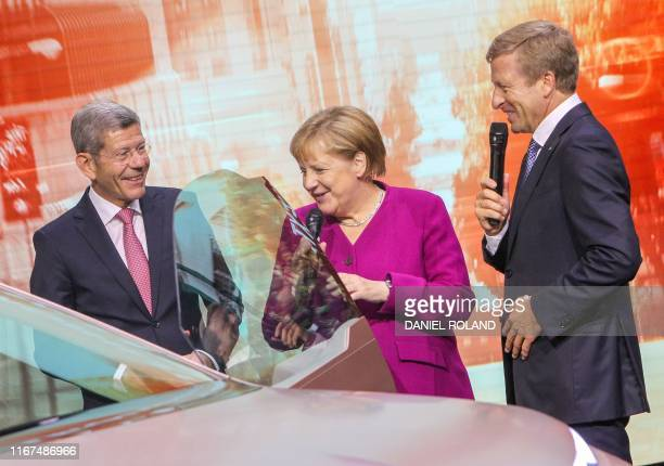 German Chancellor Angela Merkel looks at a BMW Vision iNext concept car with the CEO of German carmaker BMW Oliver Zipse and the President of the...