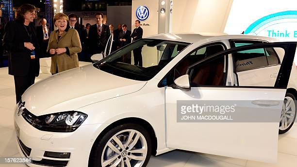 German Chancellor Angela Merkel looks at a Golf VII car as she visits the booth of German car maker Volkswagen during her tour of the fair hall at a...