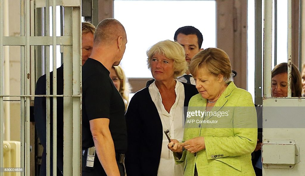 German Chancellor Angela Merkel (C-R) looks at a key as she stands next to the Federal Government's Commissioner for Culture and the Media Monika Gruetters (C) during a visit at the Berlin-Hohenschönhausen Memorial at the site of a former prison of the East German Ministry of State Security (MfS; 'Stasi') in Berlin on August 11, 2017. Thousands of political prisoners passed through this jail, including nearly all the prominent figures who opposed the regime of the German Democratic Republic (GDR). / AFP PHOTO / POOL / Wolfgang Kumm