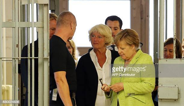 German Chancellor Angela Merkel looks at a key as she stands next to the Federal Government's Commissioner for Culture and the Media Monika Gruetters...