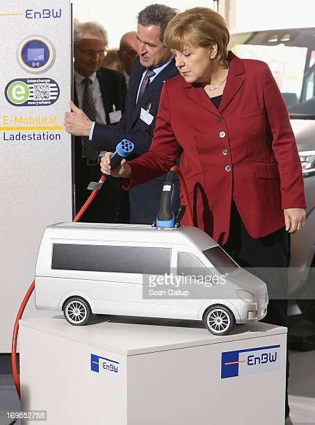 German Chancellor Angela Merkel looks at a plug used for charging an electric car while visitng the EnBW stand at the ElectroMobility Conference at...
