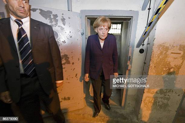 German Chancellor Angela Merkel looks at a prison cell as she visits the memorial site at the former Stasi East German secret police at the eastern...