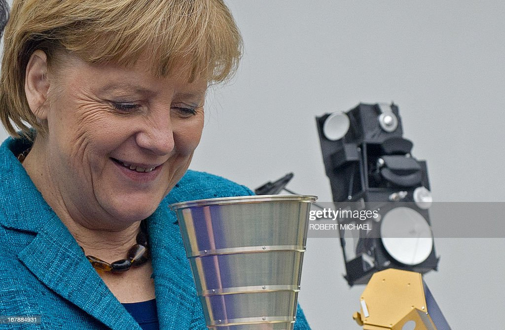 German Chancellor Angela Merkel looks at an Autonomous Star Sensor, a flight proven sensor autonomous star tracking system for long-term GEO and LEO missions for telecommunication, science and Earth observation satellites during a visit at the Jena-Optronik GmbH (Ltd) on May 2 , 2013 in Jena, eastern Germany.