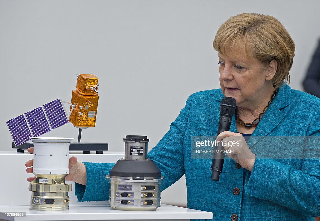 German Chancellor Angela Merkel looks at Autonomous Star Sensors, that are flight proven sensor autonomous star tracking systems for long-term GEO and LEO missions for telecommunication, science and Earth observation satellites during a visit at the Jena-Optronik GmbH (Ltd) on May 2 , 2013 in Jena, eastern Germany.