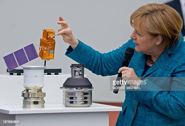 German Chancellor Angela Merkel looks at flight proven sensor autonomous star tracking system for longterm GEO and LEO missions for telecommunication...