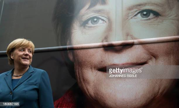 German Chancellor Angela Merkel looks at her picture displayed on an election campaign bus of the German Christian Democratic Union party in Berlin...