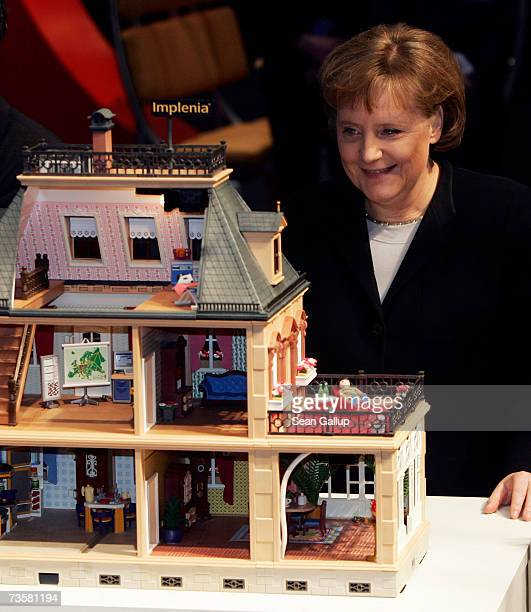 German Chancellor Angela Merkel looks into a dollhouse meant to represent an eco-friendly, microchip-equipped house at the IBM stand while touring...