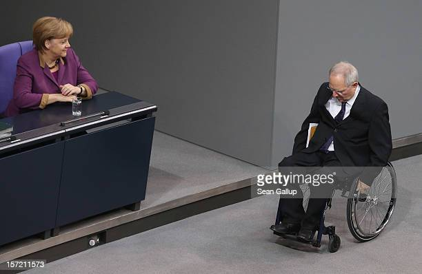 German Chancellor Angela Merkel looks on as Finance Minister Wolfgang Schaeuble finished speaking during debates over a financial aid package for...