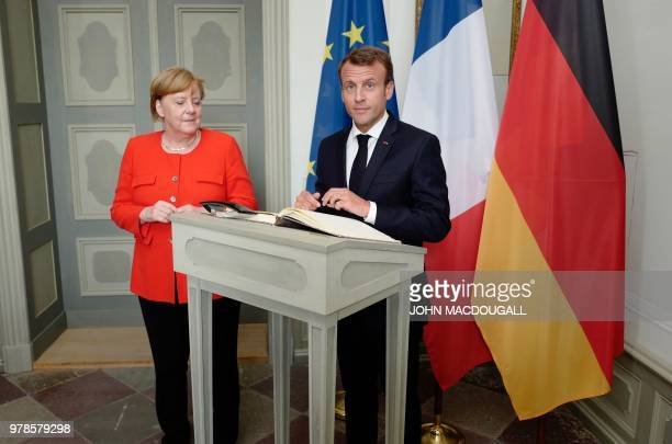 German Chancellor Angela Merkel looks on as French President Emmanuel Macron signs the guest book prior to bilateral talks at Meseberg Palace...