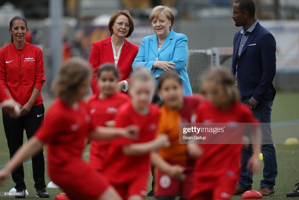 German Chancellor Angela Merkel (in blue) looks on as young girls scrimage during a program to encourage integration of children with foreign roots through football as former football star Cacau (R) and Federal Commissioner for Migration, Refugees and Integration Annette Widmann-Mauz (L of Merkel) look on at the SV Rot-Weiss Viktoria Mitte 08 sport club on June 13, 2018 in Berlin, Germany. Merkel is hosting an intergration summit at the Chancellery later today.