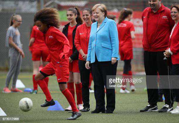 German Chancellor Angela Merkel looks on as young girls scrimage during a program to encourage integration of children with foreign roots through...