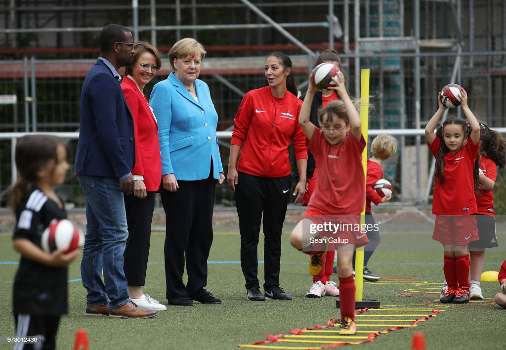 German Chancellor Angela Merkel (in blue) looks on as young girls train during a program to encourage integration of children with foreign roots through football as former football star Cacau (L) and Federal Commissioner for Migration, Refugees and Integration Annette Widmann-Mauz (L of Merkel) look on at the SV Rot-Weiss Viktoria Mitte 08 sport club on June 13, 2018 in Berlin, Germany. Merkel is hosting an intergration summit at the Chancellery later today.