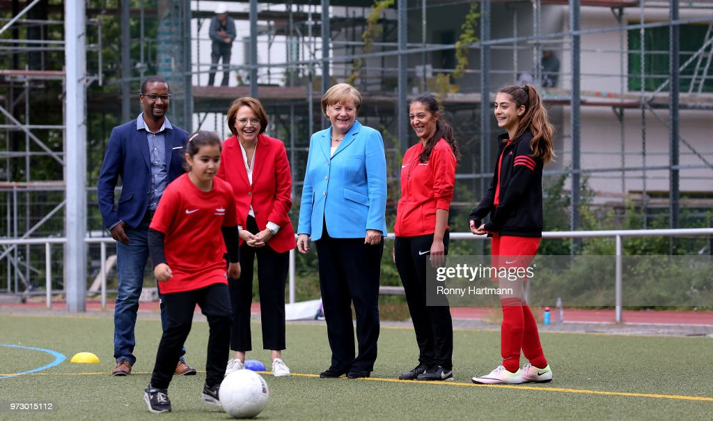 German Chancellor Angela Merkel (C) looks on as young girls train during a program to encourage integration of children with foreign roots through football as former German National player Cacau (L-R), Federal Commissioner for Migration, Refugees and Integration Annette Widmann-Mauz, coach Birguel Erbay and 13 years old player Eyleen Turan look on at the SV Rot-Weiss Viktoria Mitte 08 on June 13, 2018 in Berlin, Germany.