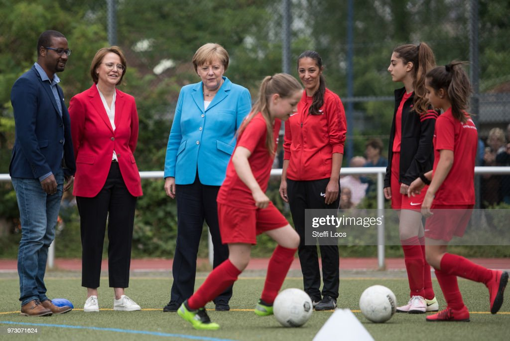 German Chancellor Angela Merkel (C) looks on as young girls train during a program to encourage integration of children with foreign roots through football as former German National player (L-R) Cacau, Federal Commissioner for Migration, Refugees and Integration Annette Widmann-Mauz, coach Birguel Erbay and 13 years old player Eyleen Turan look on at the SV Rot-Weiss Viktoria Mitte 08 on June 13, 2018 in Berlin, Germany. Merkel is hosting an intergration summit at the Chancellery later today.