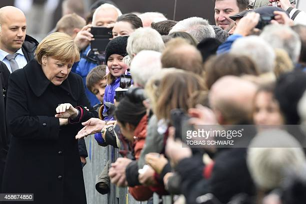 German Chancellor Angela Merkel looks on her watch as she greets visitors for commemorations to mark the 25th anniversary of the fall of the Berlin...